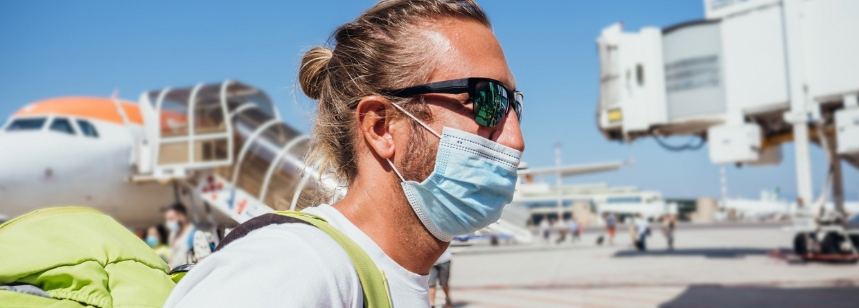 Man bij luchthaven die met vliegtuig reist tijdens pandemie van Coronavirus