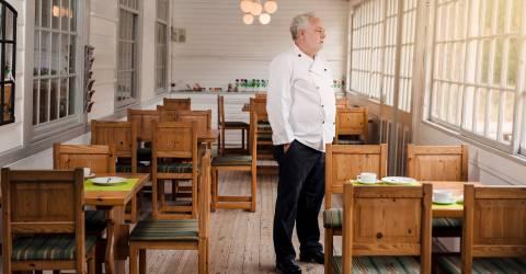 Bezorgde restauranteigenaar die zich in zijn leeg restaurant bevindt
